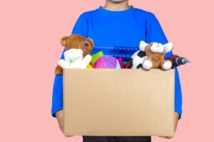 Donation concept. Kid holding donate box with clothes, books and toys.